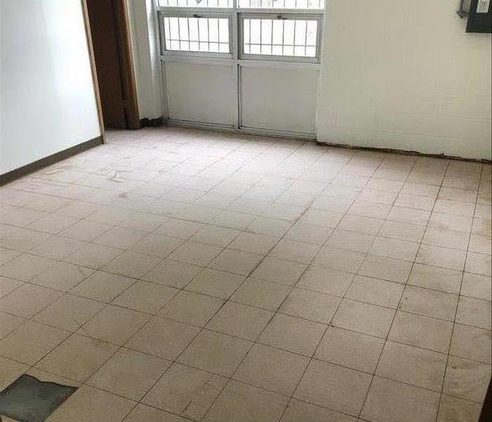 A large empty room in a commercial space has a tile floor that is covered in dirt and dust.