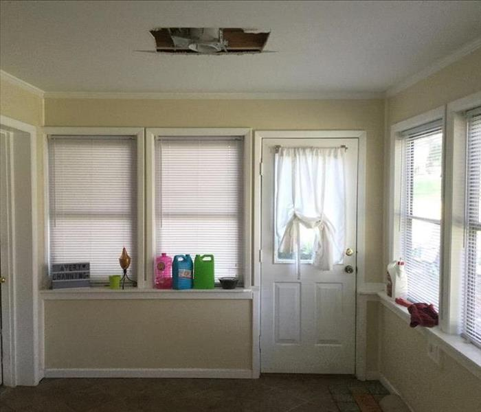 A small sun room has a hole cut out of the ceiling where water leaked in and affected the ceiling and floor.