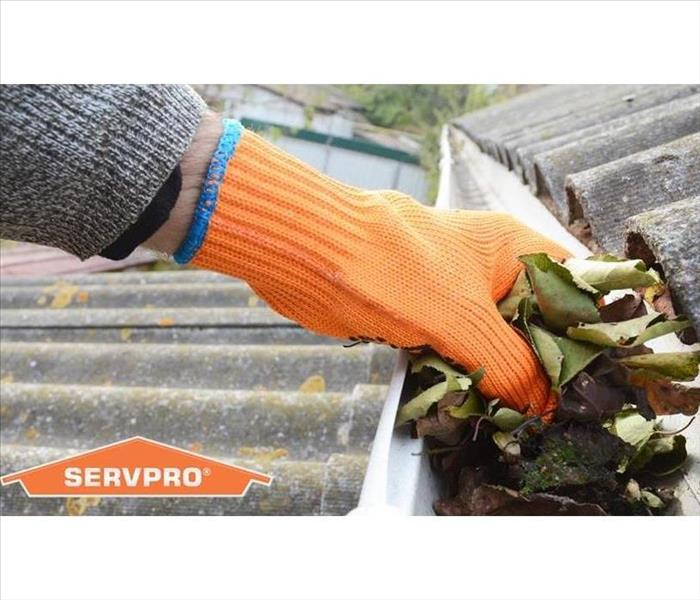 A human hand wearing a work glove is reaching in to a gutter and pulling out debris.