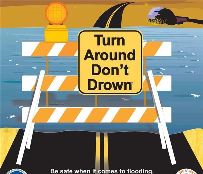 "A sign in front of flood waters on a road says ""Turn Around, Don"