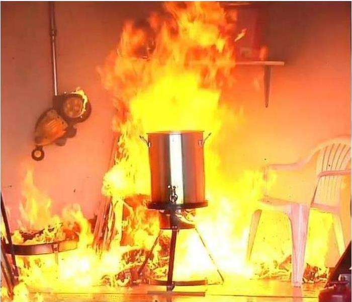 A pot to deep fry a turkey is in the middle of a room and has caught on fire.