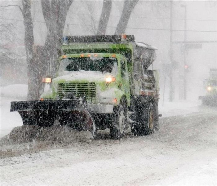 A snow plow is driving down a residential street in the middle of a snow storm.