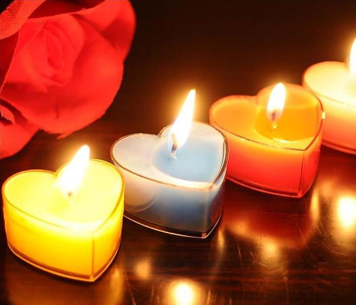 There are four lit heart shaped tea candles in a row with a rose behind them